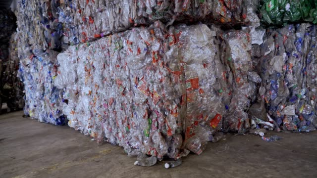 background of stack cubes of crushed clear plastic bottles waiting for process in a recycling center. - hay bail stock videos & royalty-free footage