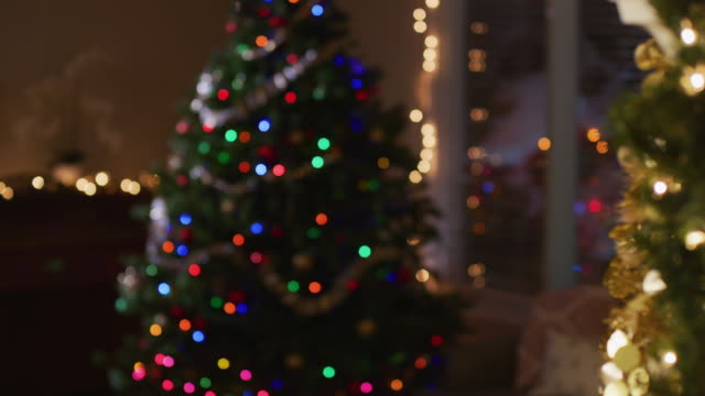 background plate; out-of-focus christmas tree stands in an empty living room with orange, green, red and blue lights. - lametta stock-videos und b-roll-filmmaterial