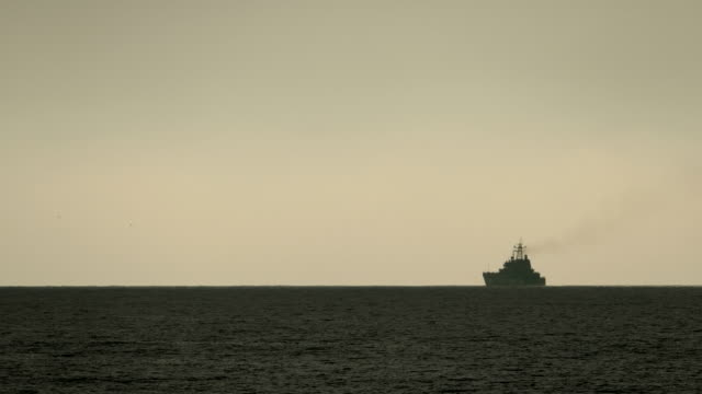 background - silhouette of a warship in the evening sea - convoy stock videos and b-roll footage