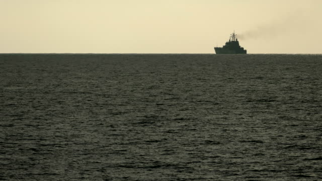 Background - silhouette of a warship in the sea at the horizon