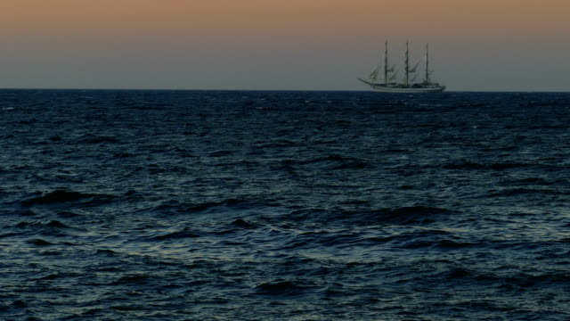 background - sunset and a beautiful sailing ship in full sail - veliero video stock e b–roll