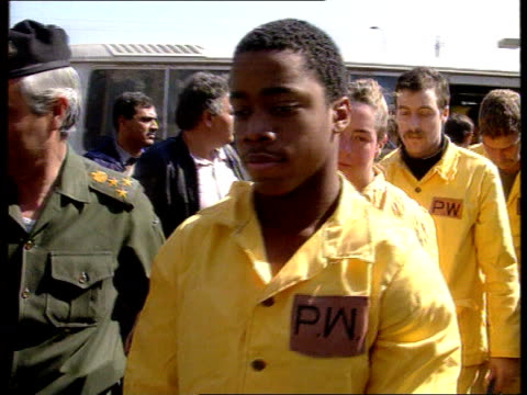 backgrounder on war crimes: bosnian prison camps; itn lib iraq: baghdad: ext cms line of allied pows in yellow boiler suits towards & past as being... - ダーモット・マーナハン点の映像素材/bロール