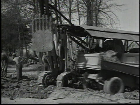 vídeos y material grabado en eventos de stock de backhoe dumping dirt into a truck / bulldozer moving earth in wooded area / men operating heavy machinery - 1934