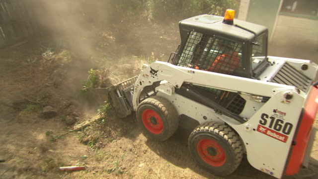 backhoe in home renovation backyard construction landscaping site with bobcat clearing rubble concrete cutter in background / bobcat scooping up... - renovierung themengebiet stock-videos und b-roll-filmmaterial