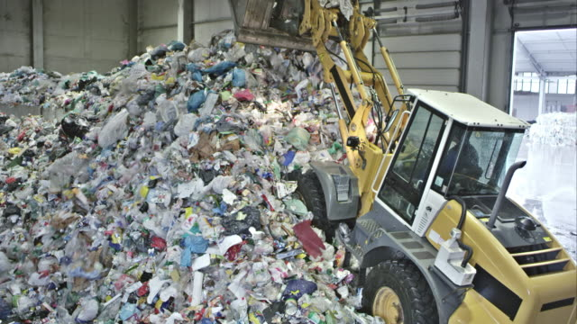 TS backhoe loader piling up plastic waste in recycling facility