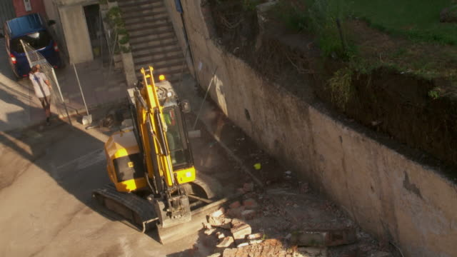 backhoe loader shifting rubble at construction site - rubble stock-videos und b-roll-filmmaterial