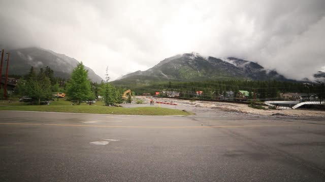 / backhoes and cleanup crew on roadways after flood / 'Road Closed' sign / high waters of Cougar Creek