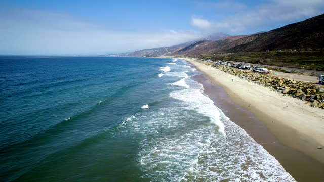 vídeos de stock e filmes b-roll de backing up over beach california coast aerial drone view - alto contraste