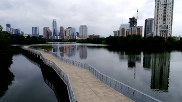 vídeos de stock e filmes b-roll de backing up over bridge with a crowd of kayakers along town lake with austin , texas skyline cityscape view in the background perfect reflections on the water - town