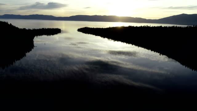vídeos de stock e filmes b-roll de backing up over fannette island at emerald bay lake tahoe mirrored reflection sunrise - reflection