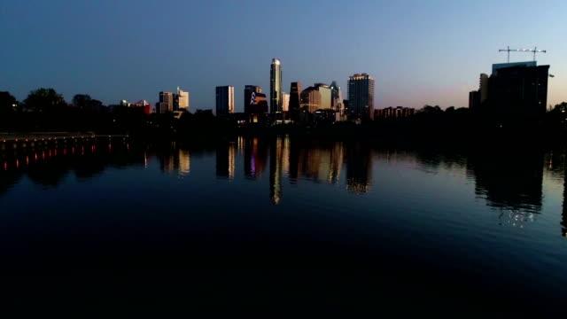 vídeos de stock e filmes b-roll de backing up over water austin texas mirrored downtown cittyscape perfection - town