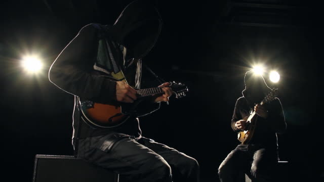 2 backlit anonymous musicians playing mandolin live - chiaroscuro stock videos and b-roll footage