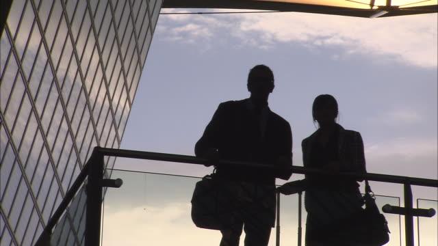 stockvideo's en b-roll-footage met ms backlit couple standing by railing in airport/ munich, germany - münchen vliegveld