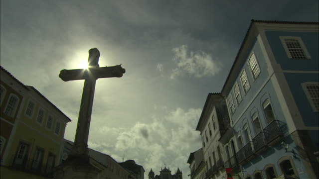 vídeos de stock, filmes e b-roll de la ms backlit cross in town square between two rows of building under overcast sky/ brazil - praça