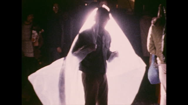 backlit man covers himself with a plastic sheet ; 1972 - 1972 stock videos & royalty-free footage