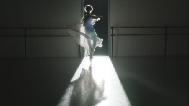 Backlit shot of ballerina performing Pirouette on pointe as she comes towards camera