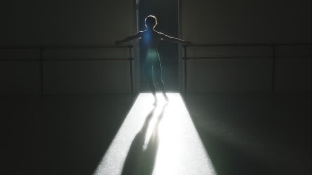 vídeos de stock, filmes e b-roll de backlit shot of male ballet dancer performing pirouette on pointe - pirouette
