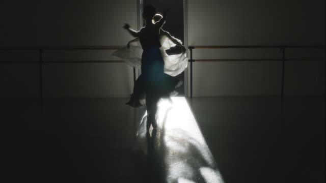 Backlit shot of three ballet dancers performing Pirouettes towards camera