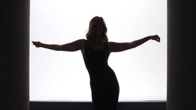 vidéos et rushes de backlit slow motion woman doing a sexy dance - corps humain
