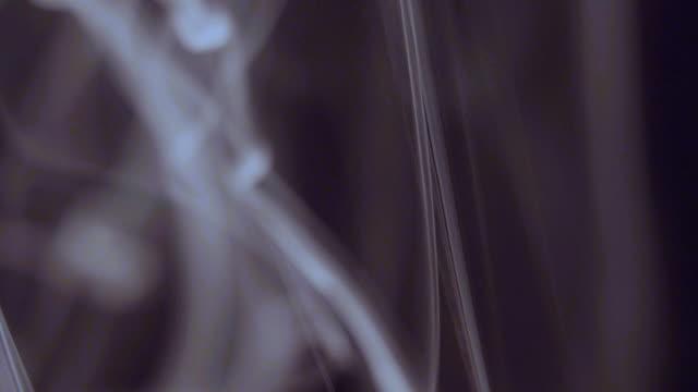 Backlit smoke on black background slow motion