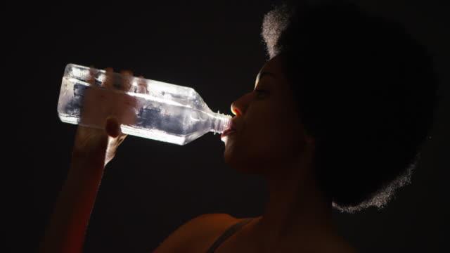 Backlit studio shot of woman drinking water from bottle