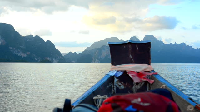 backpack bag on boat in cheow lan lake, thailand - longtail boat stock videos & royalty-free footage