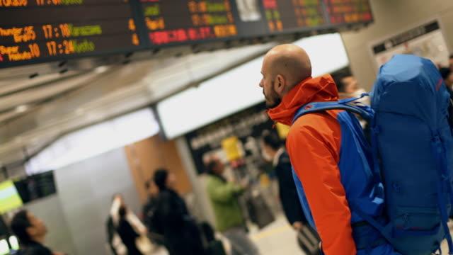 空港でバックパッカー - 発着案内板点の映像素材/bロール