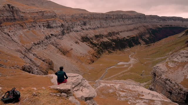 backpacker contemplating the view in the rocky terrain during autumn in ordesa valley in the spanish pyrenees. spain. otoño en el parque nacional de ordesa. - extreme terrain stock videos & royalty-free footage