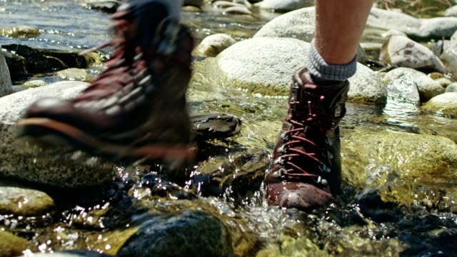 Backpacker crossing the stream. Close up on hiking boots