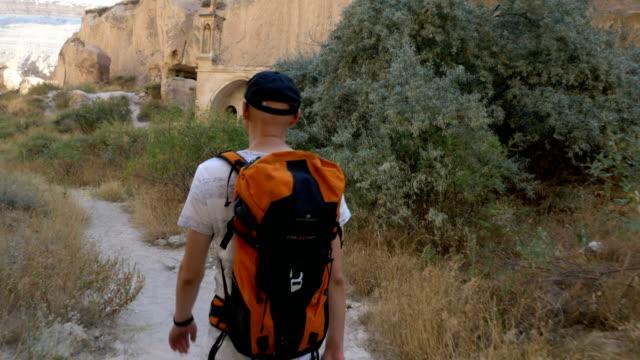 Backpacker is walking in the Zelve Valleys And Open Air Musuem in Cappadocia