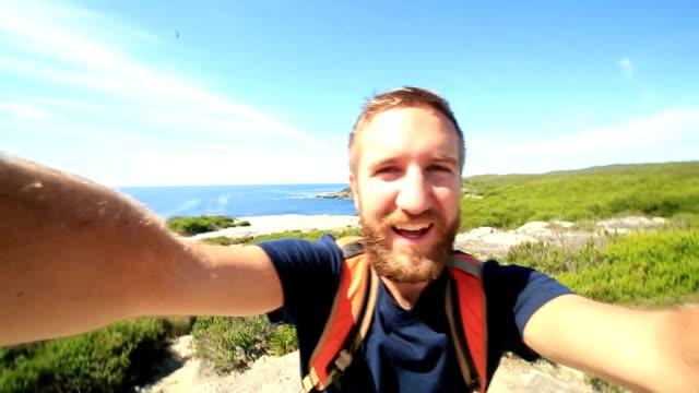 Backpacker man takes a selfie portrait by the sea