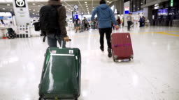 SLO MO - Backpacker rushing to boarding while pulling their luggage