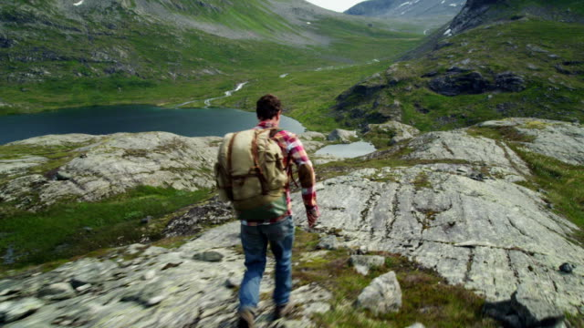 backpacker trekking. man running on rocky coast - north stock videos and b-roll footage