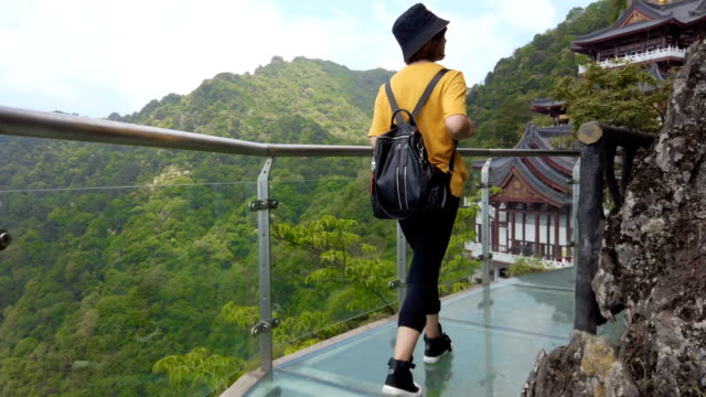 backpacker walking along glass skywalk in mountain landscape - elevated walkway stock videos & royalty-free footage