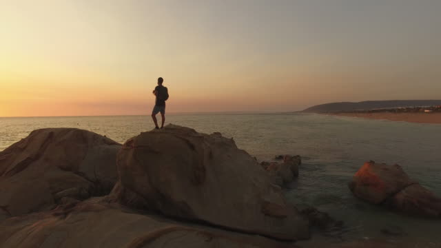 backpacker walking in the sea shore of a beach at sunset - klippe stock-videos und b-roll-filmmaterial