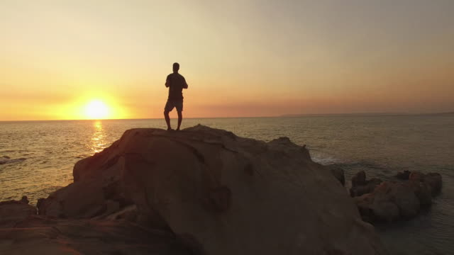 backpacker walking in the sea shore of a beach at sunset - cádiz stock videos and b-roll footage