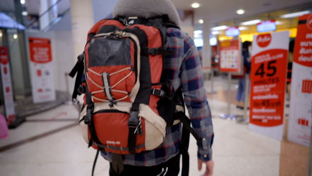 backpacker walking to check-in counter in airport with holding smartphone - rucksack stock videos & royalty-free footage