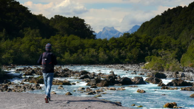 backpacker walking towards a river in the forest - rucksack stock-videos und b-roll-filmmaterial