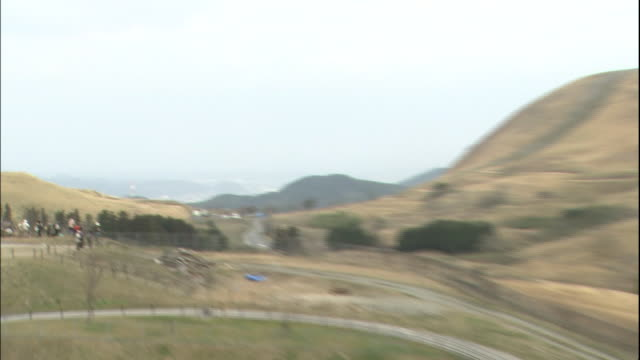 backpackers and photographers stand on a hillside; men burn dry grass in a field. - 緊急用具点の映像素材/bロール