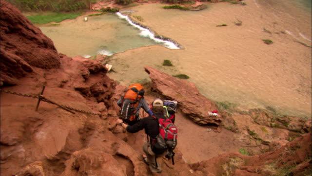 vídeos de stock e filmes b-roll de backpackers climb down a steep trail in the grand canyon. - peitoril de janela