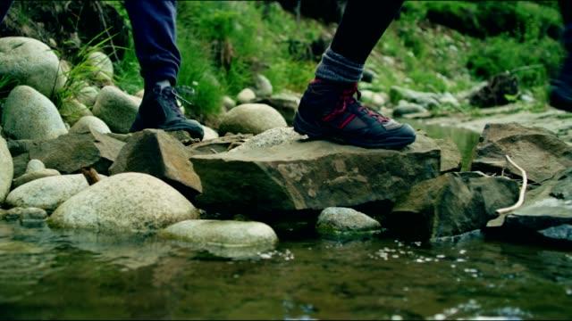 Backpackers overschrijding van de stream. Close-up op wandelschoenen