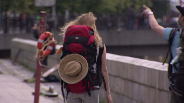 vídeos y material grabado en eventos de stock de backpackers talk and point whilst walking next to the river liffey, dublin, ireland. - curiosidad