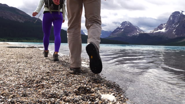 Backpacking couple bound across stepping stones, mountain lake