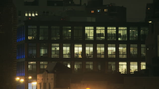 ms backplate of midrise loft building with activity visible in windows in meatpacking district at night / new york, new york, usa - 屋根裏部屋点の映像素材/bロール