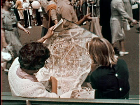 backs of woman and girl sitting on bench looking at map of new york world's fair grounds/ queens ny - 1964年点の映像素材/bロール