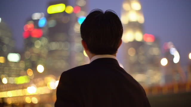 ms backshot of businessman looking at city at night - 立つ点の映像素材/bロール