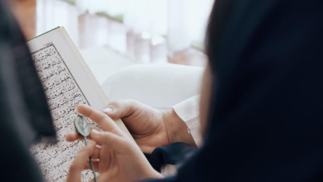 vidéos et rushes de backshot de la famille lisant le livre de prière ensemble. - islam