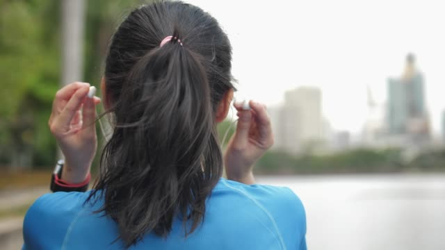 backside footage of a girl putting on the headphones - cuffia attrezzatura per l'informazione video stock e b–roll