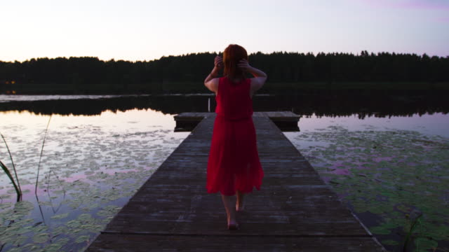 vidéos et rushes de backside view of woman in red dress walking through high reeds and enjoying sunset at river - robe rouge