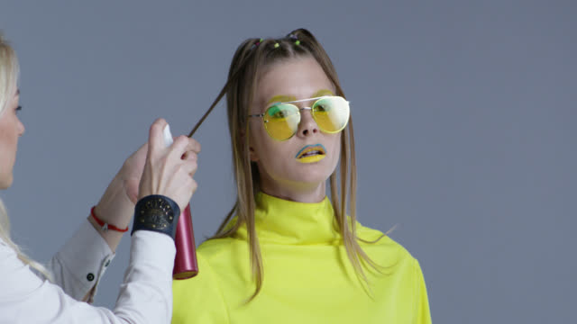 backstage. hairdresser fixes model`s hairstyle. model wears yellow sunglasses. fashion video. - catwalk stock videos & royalty-free footage